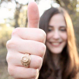 girl giving thumbs up wearing gold ring