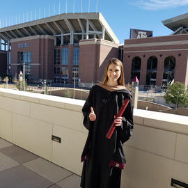 texas a&m graduate standing in front of kyle field with a thumbs up