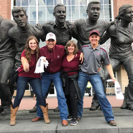 family with arms over each other's shoulders posing for photo in front of statue