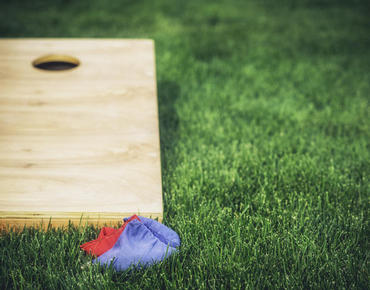 cornhole board and bean bags on grass