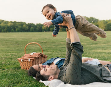 mom and dad laying in grass as dad holds baby above them