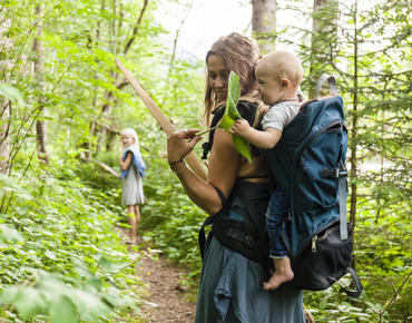 mom with baby in a back carrier walking on a forest trail