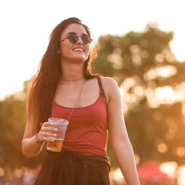 girl in red tank top holding a beer and smiling