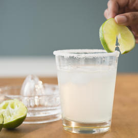 person placing a lime slice onto the edge of a margarita glass