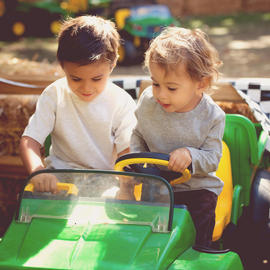 two kids riding toy tractor