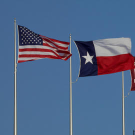 american flag and texas state flag flying against blue sky