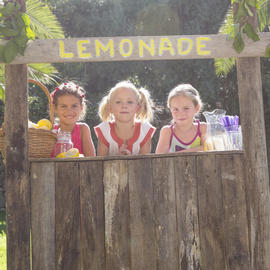 three girls sitting behind a lemonade stand