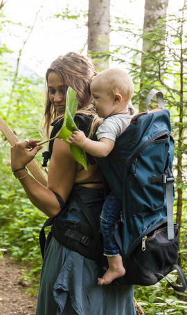 mom with baby in back carrier showing baby leaf