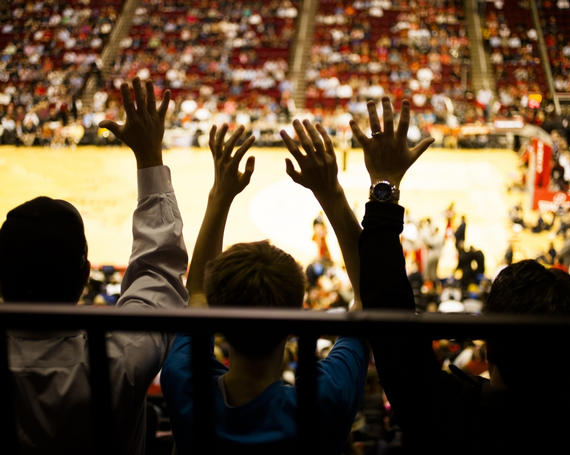 fans cheering from the bleachers of a basketball game