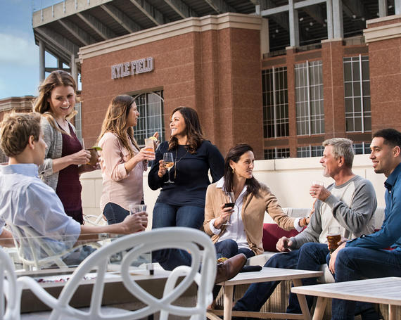 group of people drinking and talking on rooftop patio