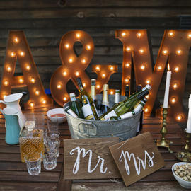 a and m letters lit up on a table with a bucket of wine bottles and