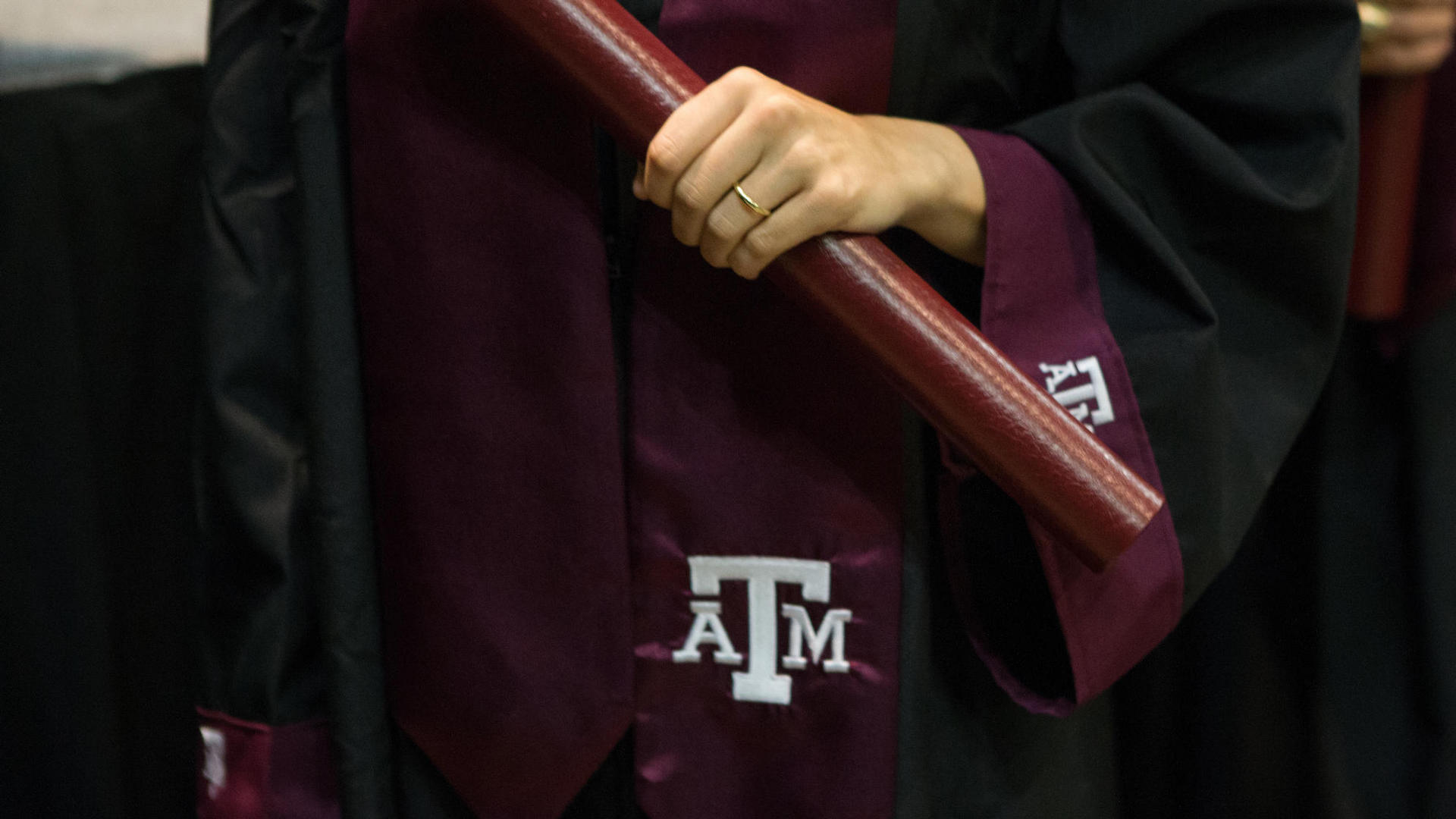 texas am graduate holding diploma roll