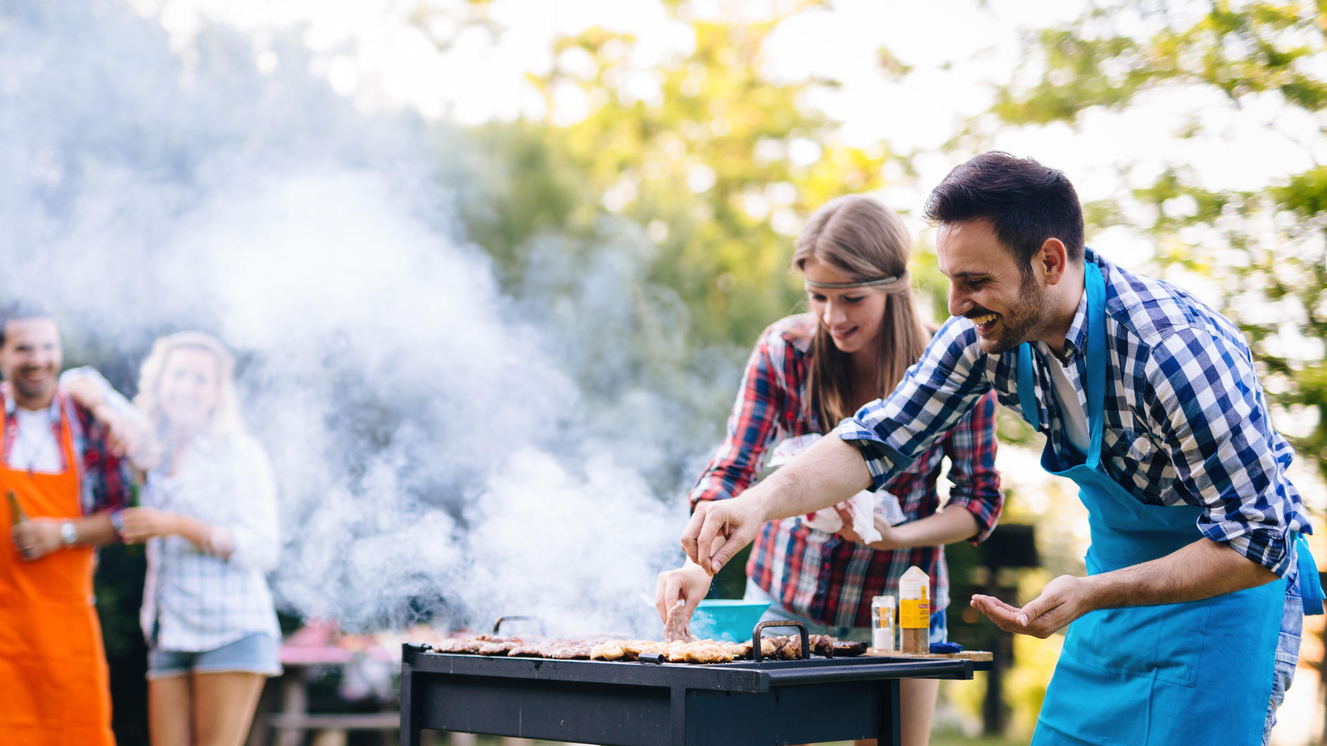 couple grilling at a backyard barbeque