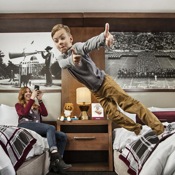 kid jumping off bed showing thumbs up